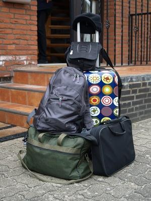 Koffer und Taschen vor einem Haus