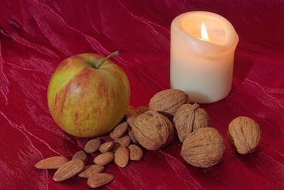 Apfel, Kerze, Nüsse un Mandeln auf roter Samtdecke