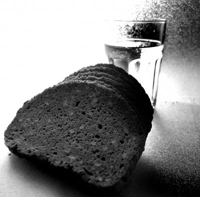 Glas Wasser und Scheiben von Schwarzbrot in Schwarz-Weiss