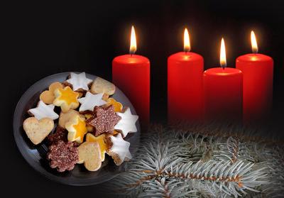 Vier brennende Adventskerzen und Gebäck